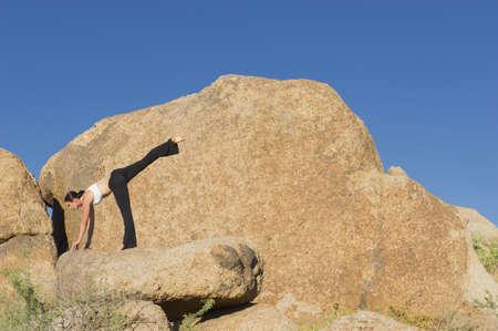 Caucasian woman practicing yoga on rock formation