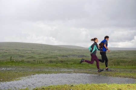 Caucasian couple jogging on gravel path in rural field