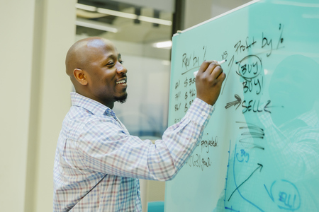 Black businessman writing on whiteboard LANG_EVOIMAGES