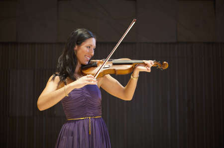 Caucasian musician playing violin on stage LANG_EVOIMAGES