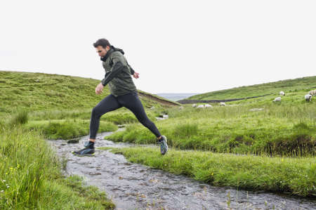 Caucasian man jumping over creek in rural field