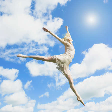 Caucasian ballerina leaping under clouds