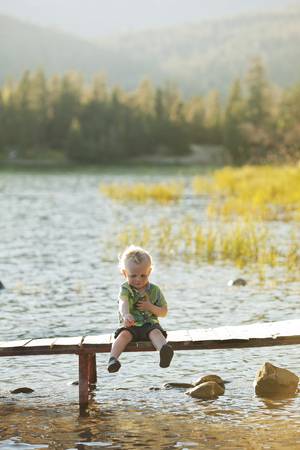 Caucasian boy sitting on wooden deck over lake
