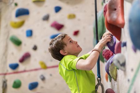Caucasian boy climbing rock wall indoors LANG_EVOIMAGES