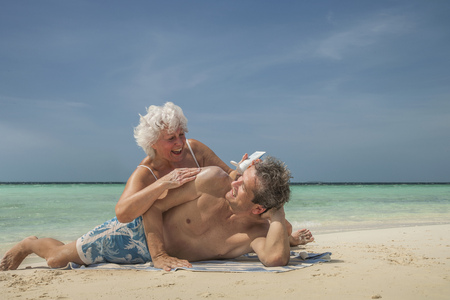 Older Caucasian couple relaxing on beach