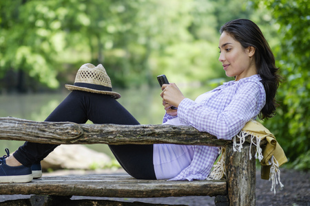 Hispanic woman using cell phone on park bench