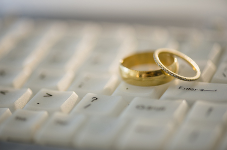 Close up of wedding rings on computer keyboard LANG_EVOIMAGES