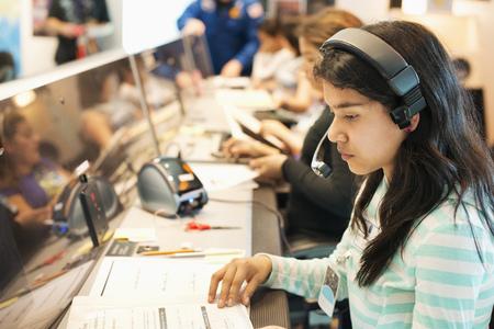 Hispanic student listening to headset at desk LANG_EVOIMAGES