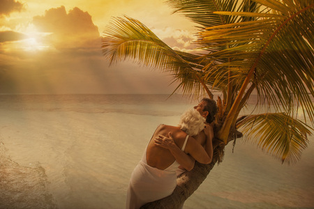 Older Caucasian couple hugging on palm tree at beach LANG_EVOIMAGES
