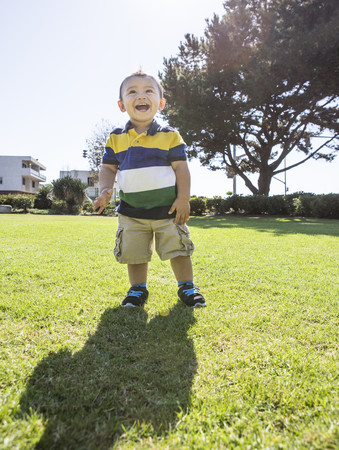 Hispanic boy standing on grass in park