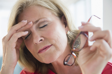 Stressed Caucasian woman rubbing forehead LANG_EVOIMAGES