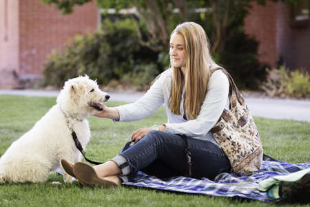 Student petting dog on college campus LANG_EVOIMAGES
