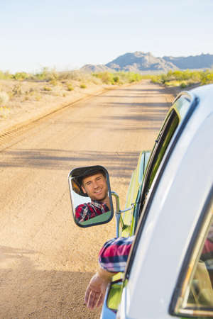 Reflection in side-view mirror of Caucasian man driving truck