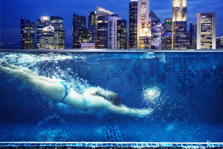Caucasian woman swimming in urban rooftop pool in Singapore cityscape LANG_EVOIMAGES