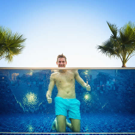 Caucasian man giving thumbs up in swimming pool