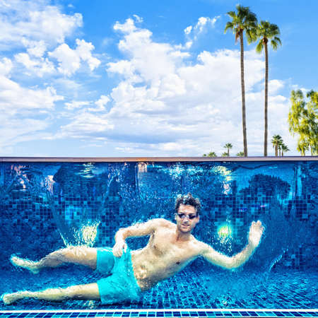 Caucasian man waving in swimming pool LANG_EVOIMAGES