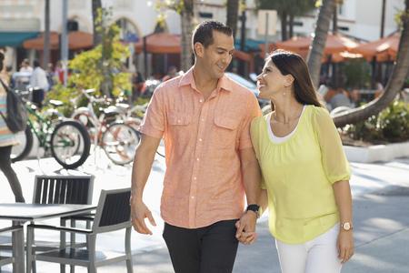 Hispanic couple holding hands on sidewalk LANG_EVOIMAGES