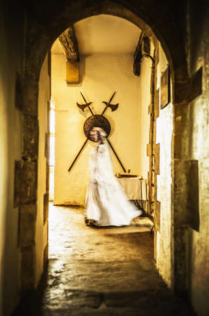 Blurred view of Caucasian woman in medieval costume walking in castle