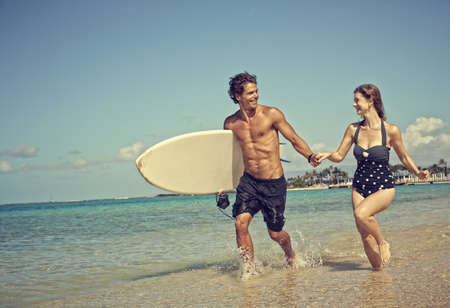 Caucasian couple running with surfboard on beach LANG_EVOIMAGES