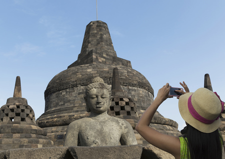 Tourist photographing Buddha statue on Temple of Borobudur, Borobudur, Indonesia LANG_EVOIMAGES