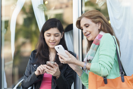 Mother and daughter using cell phones outdoors LANG_EVOIMAGES