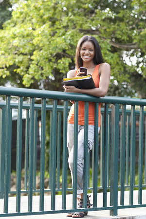 Black student using cell phone on walkway outdoors LANG_EVOIMAGES