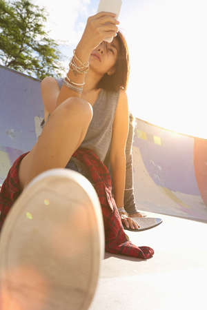 Asian woman using cell phone at skate park LANG_EVOIMAGES