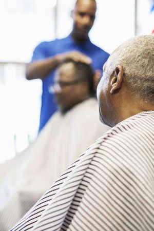 Black customer waiting for barber in retro barbershop LANG_EVOIMAGES