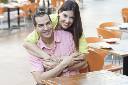 Hispanic couple hugging at sidewalk cafe LANG_EVOIMAGES