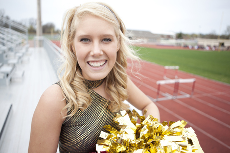 Caucasian cheerleader smiling on bleachers LANG_EVOIMAGES