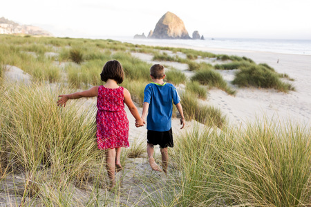 Caucasian children walking on beach