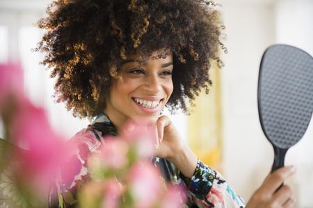 Mixed race woman admiring herself in mirror
