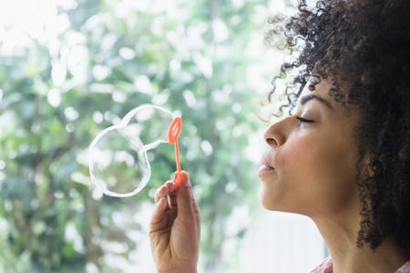Mixed race woman blowing bubbles LANG_EVOIMAGES
