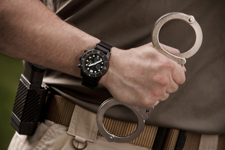 Close up of police officer holding handcuffs LANG_EVOIMAGES