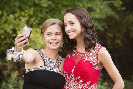 Caucasian teenage girls taking selfie with cell phone before prom