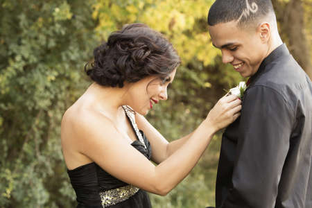 Teenage girl attaching corsage to prom date