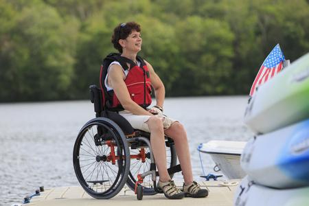 Caucasian paraplegic woman sitting on dock