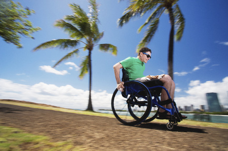 Disabled man racing in wheelchair by urban beach LANG_EVOIMAGES