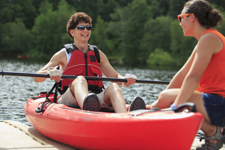 Caucasian instructor helping paraplegic woman with kayak LANG_EVOIMAGES
