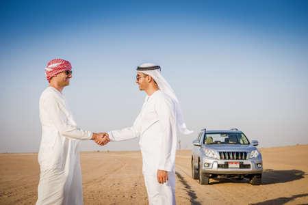 Men shaking hands in desert LANG_EVOIMAGES