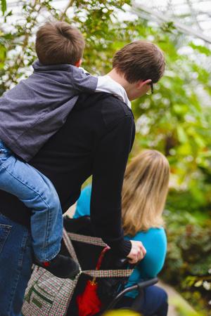 Man pushing paraplegic wife and carrying son piggyback