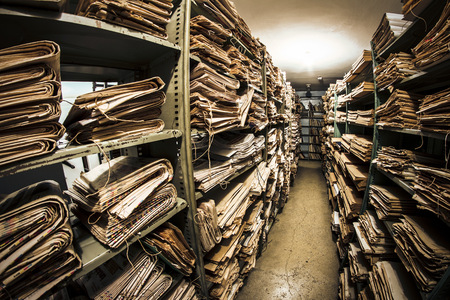 Stacks of old newspapers in library archive LANG_EVOIMAGES