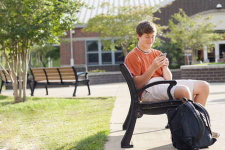 Caucasian teenage boy using cell phone on bench LANG_EVOIMAGES