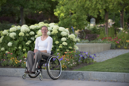 Disabled woman sitting in wheelchair on city street LANG_EVOIMAGES