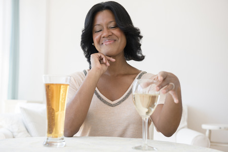 Black woman choosing between white wine and beer LANG_EVOIMAGES