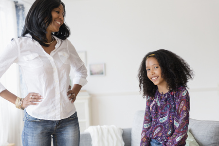 Smiling mother and daughter in living room