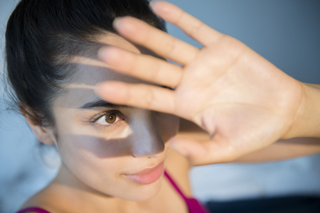 Hispanic woman shielding herself from light LANG_EVOIMAGES