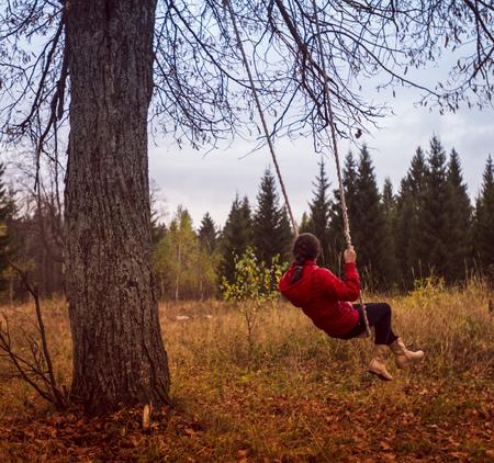 Caucasian girl playing on swing