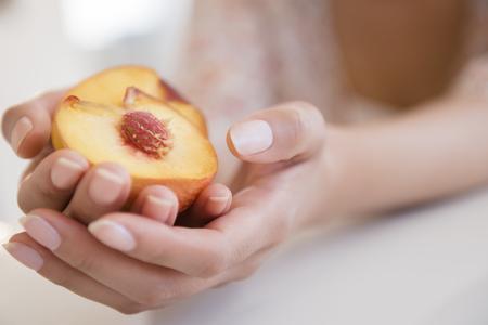 Hispanic woman holding halved peach LANG_EVOIMAGES
