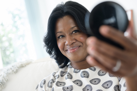 Black woman admiring herself in compact mirror LANG_EVOIMAGES